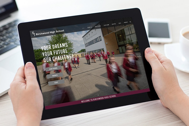 A person holding a tablet browsing through Birchwood High School website design