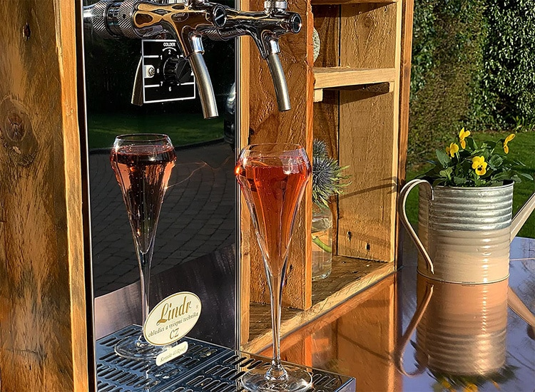 Close up of taps and glasses filled with Prosecco in Bubblicious branded Tuk Tuk