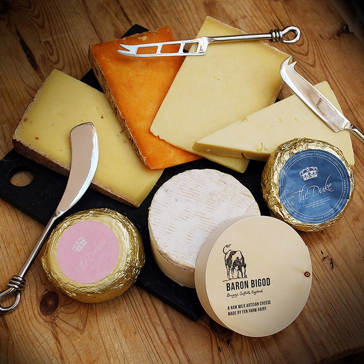 Selection of Cheese with cheese utensils resting on a black board for Cheese Plus
