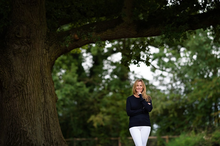Woman standing under a tree photography for Clare King