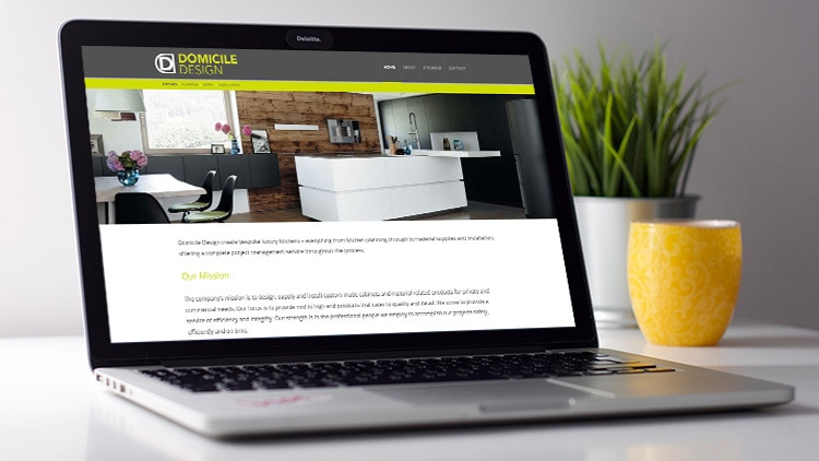 Domicile Design website on laptop screen with plants in background