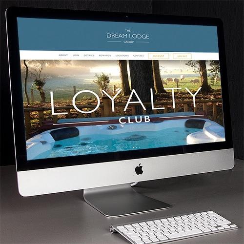 Desk lamp facing desktop computer displaying homepage of Dream Lodge Loyalty website design Thumbnail