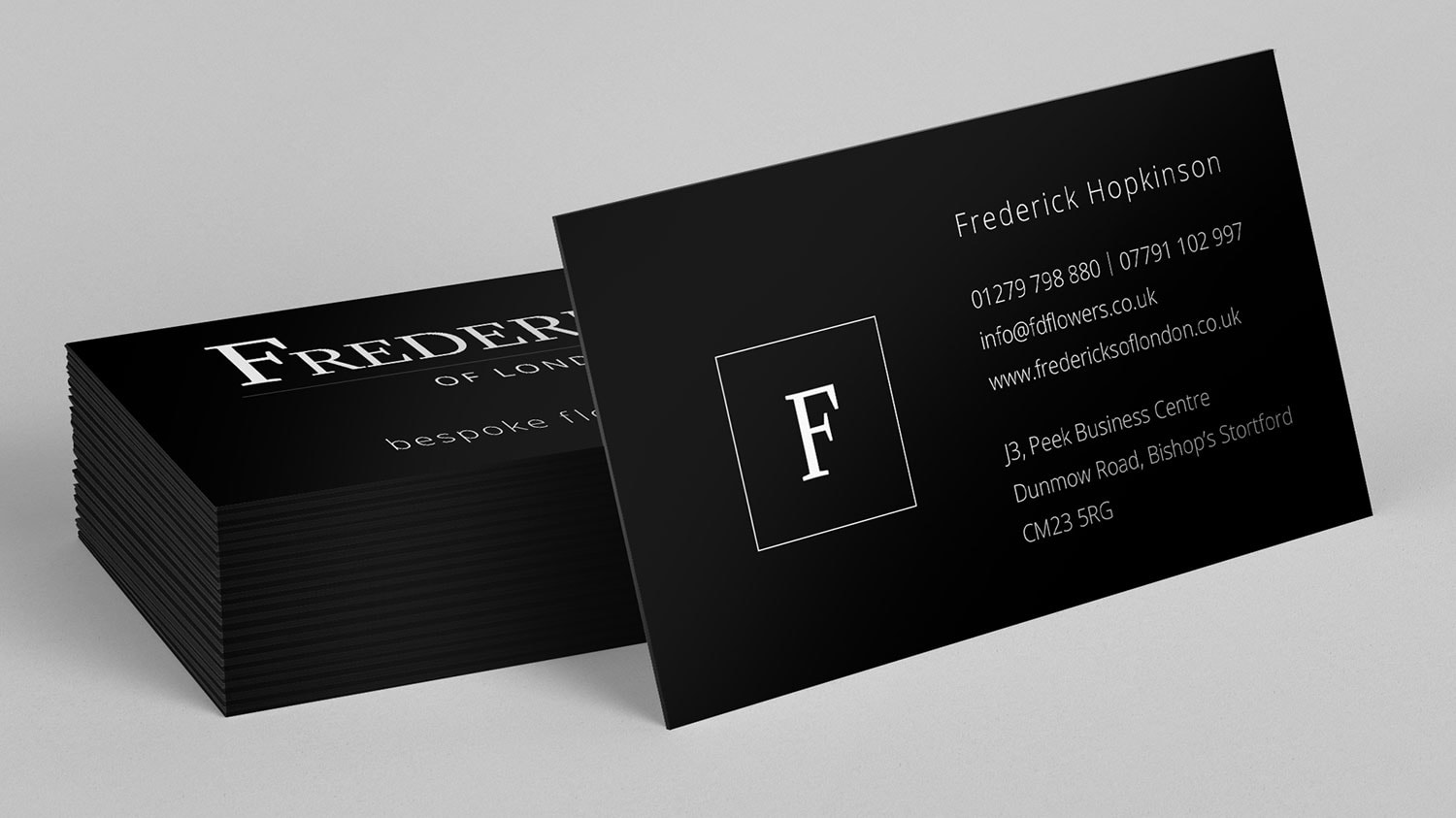 Business card resting on stack of business cards for Fredericks of London branding design