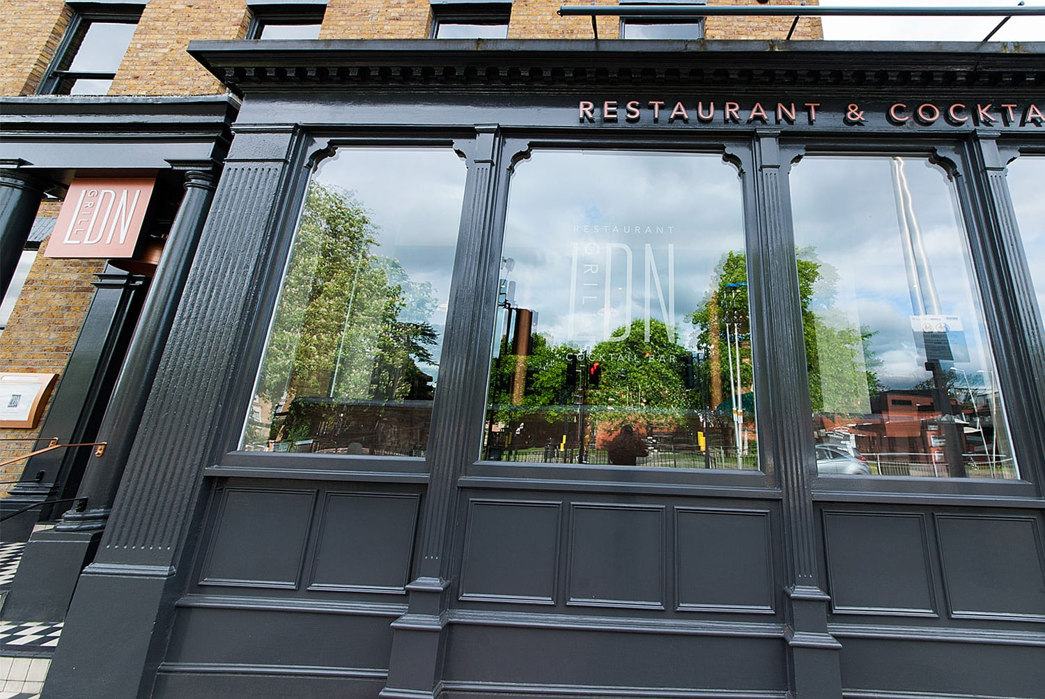 Exterior branding showing illuminated sign and window decal of LDN Grill Logo design