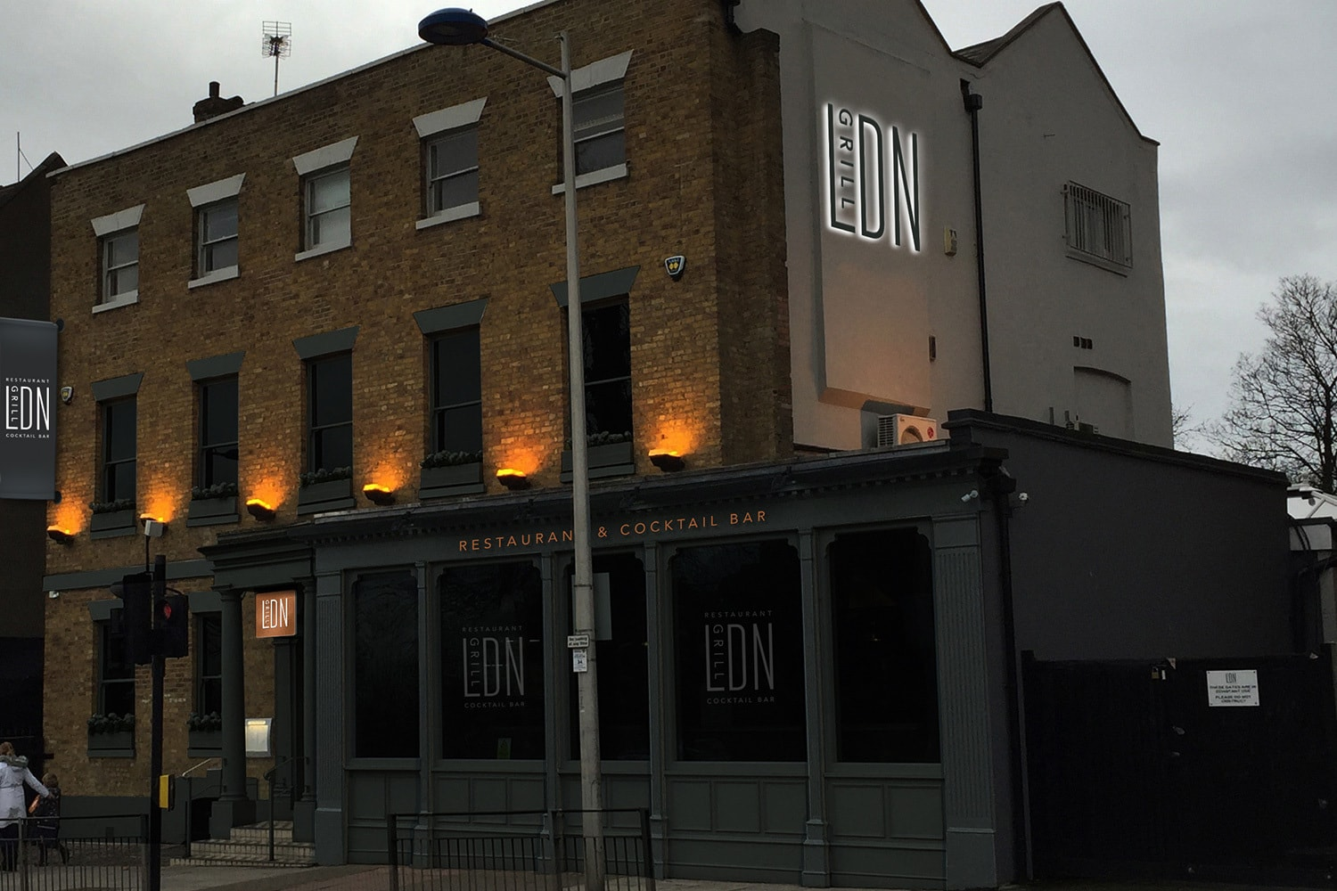 LDN grill exterior branding with an illuminated sign and projecting sign