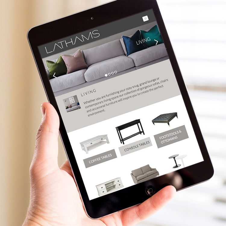 A person holding a tablet displaying the Lathams homepage website design