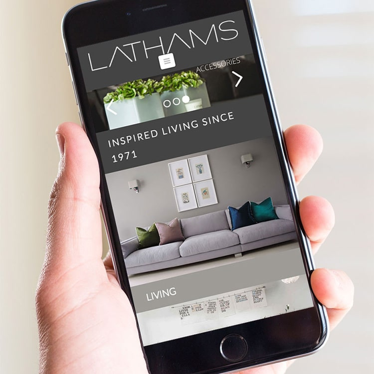 A person holding a mobile displaying the Lathams homepage website design