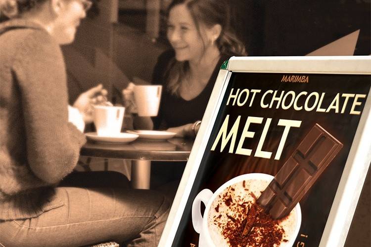 Promotion Design poster signage for Marimba's Ice Chocolate Melt in front of two people enjoying a cup of hot chocolate