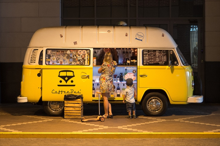 A woman and child standing in front of a yellow VW vintage van photography for Retail Reimagined