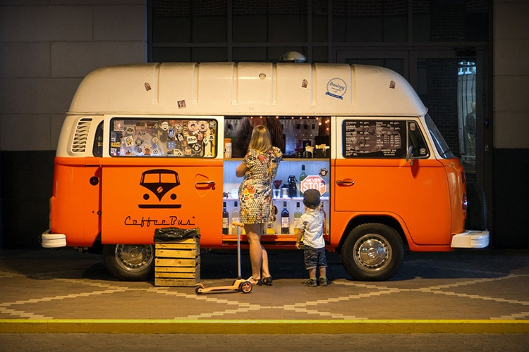 A woman and child standing in front of an orange VW vintage van retouched and enhanced photography for Retail Reimagined