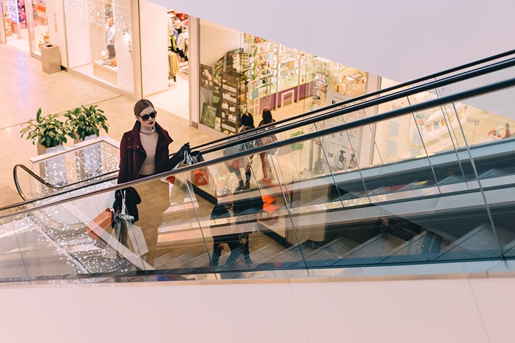 A woman going up on escalators holding shopping bags photography for Retail Reimagined