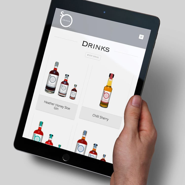 A person holding a tablet viewing the So Drinks responsive eCommerce website design