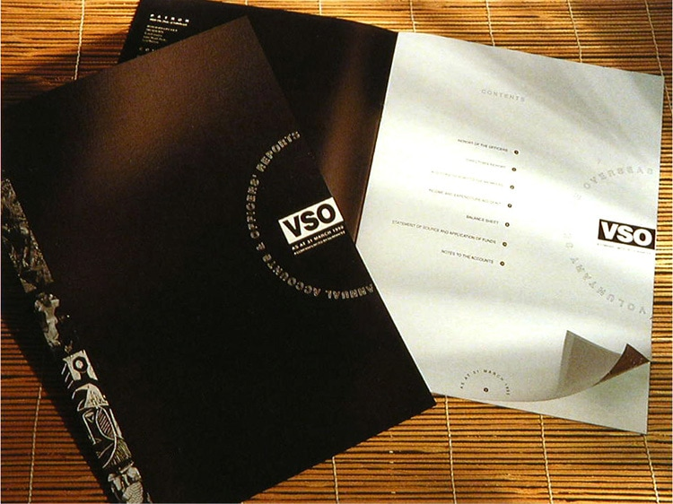 Black front cover and open spread brochure design for VSO annual accounts