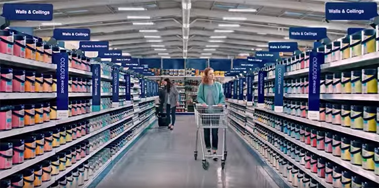 A woman with a trolley walking through paint selection photography for Wickes