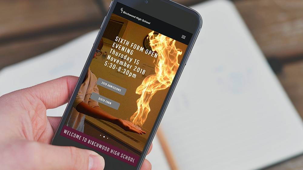 A person holding mobile displaying Birchwood High School responsive website