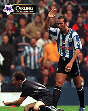 Paolo di Canio raising his hand looking at the football referee on the ground