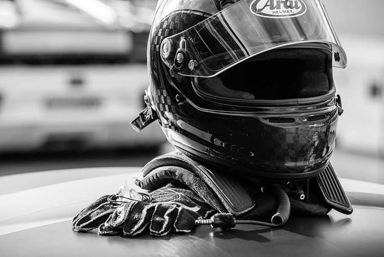 Close up of drivers helmet and gloves resting on hood of a car photography for Walero