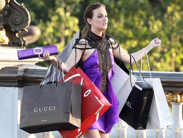Woman holding different designer shopping bags