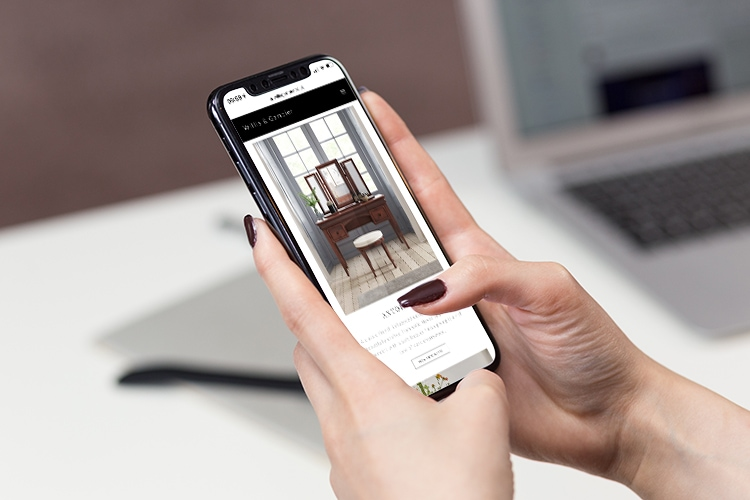 Woman holding phone viewing the new responsive Willis & Gambier website